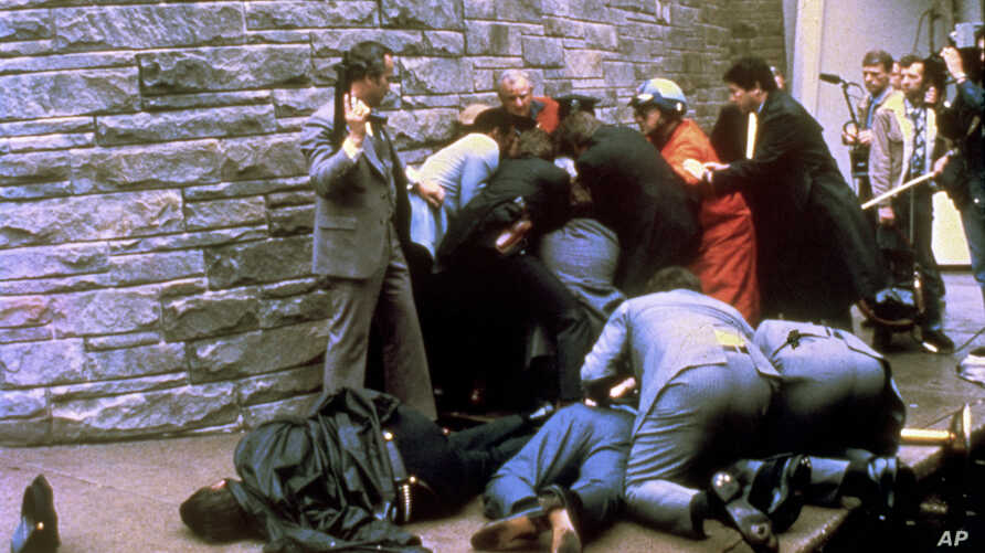 FILE - This March 30, 1981 file photo shows a U.S. secret service agent with an automatic weapon watches over James Brady, the president's secretary, after being wounded in an attempt on the life of President Ronald Reagan in Washington.  A Washingto