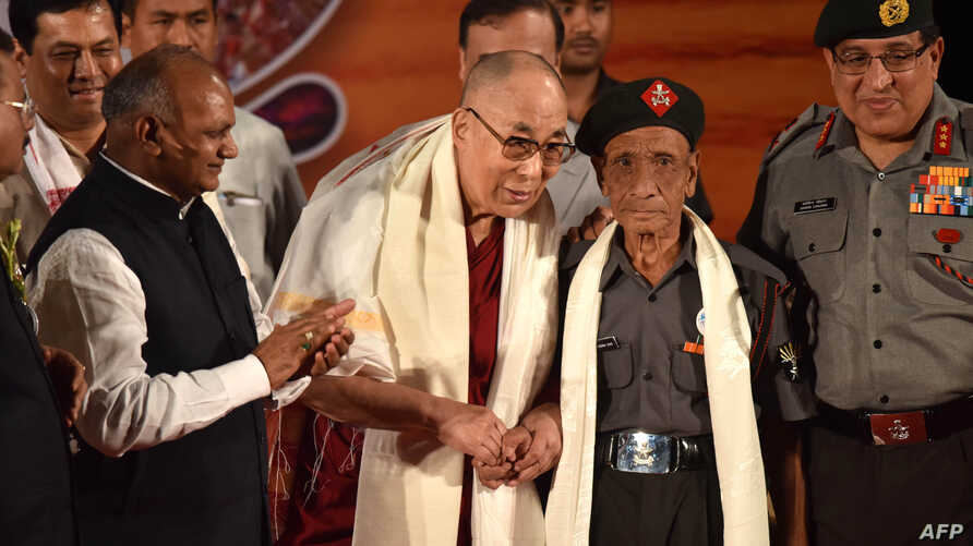 The Dalai Lama (L) shakes hands with Naren Chandra Das, the lone known survivor of a group of seven Indian guards who escorted the Tibetan spiritual leader into India nearly 60 years ago, in Guwahati, the capital of the northeastern Indian Assam stat