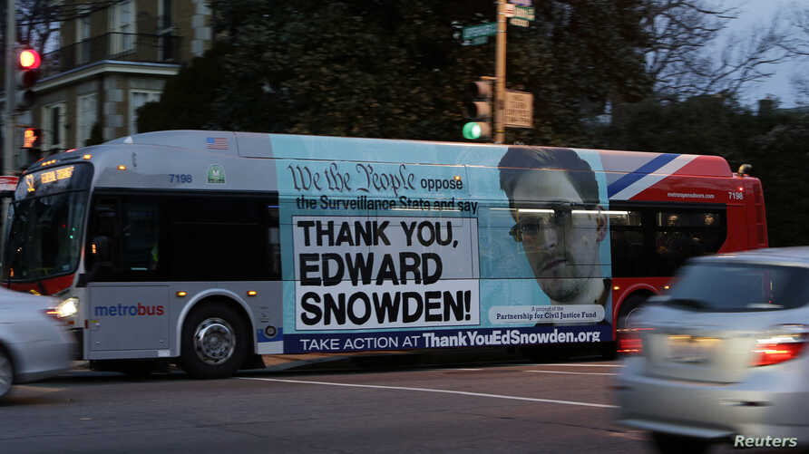 A Washington Metro bus is seen with an Edward Snowden sign on its side panel, Dec. 20, 2013.