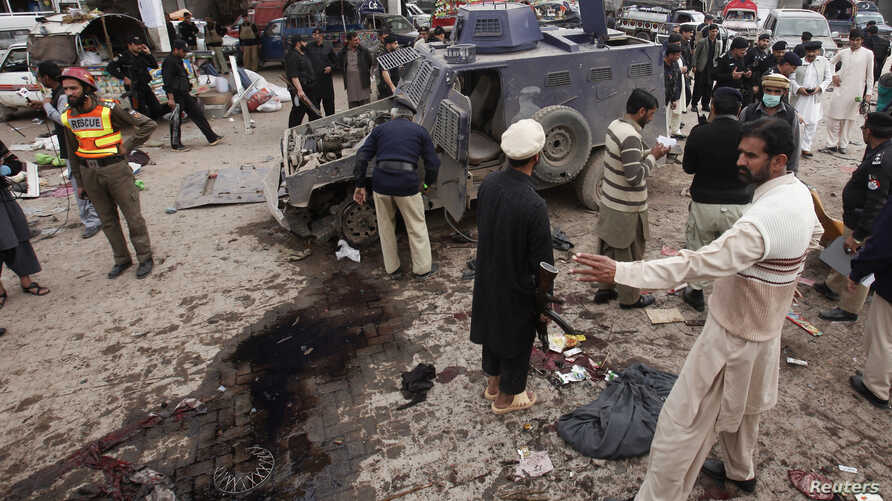 Security officials and rescue workers collect evidence at the site of a bomb blast on outskirts of Peshawar, March 14, 2014.