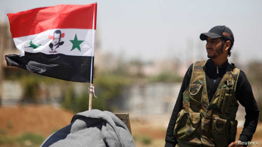 A Syrian army soldier stands next to a Syrian flag in Umm al-Mayazen, in the countryside of Daraa, Syria, July 10, 2018.