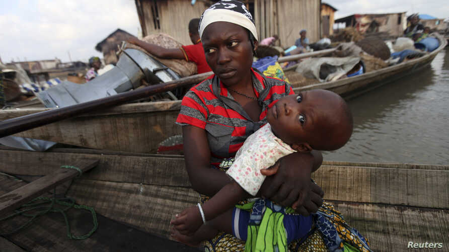 A woman sits in a canoe with her child as the metropolitan government begins the demolition of structures in the Makoko riverine community in Lagos, July 16, 2012. The structures were deemed illegal because they were built without permission on Lagos