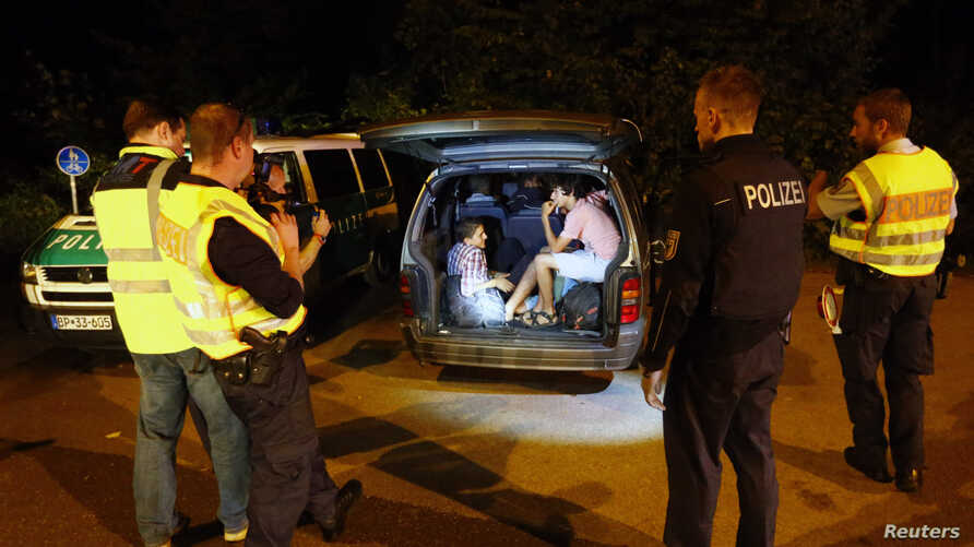 A group of migrants from Syria sits inside a vehicle stopped by German police on a country road heading to Freilassing, Germany from Salzburg, Austria Sept. 13, 2015.