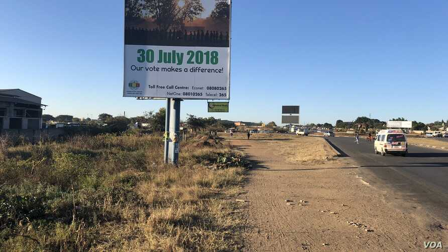 People walk past a Zimbabwe Electoral Commission billboard in Harare, July 23, 2018, urging people to go and vote on July 30 and decide their future. (S. Mhofu/VOA)