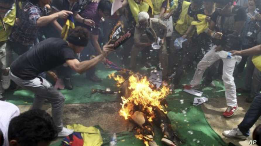 Tibetan exiles try to douse the flames from their comrade, Jamphel Yeshi, after he set himself on fire during a protest against the upcoming visit of Chinese President Hu Jintao to India in New Delhi, March 26, 2012.