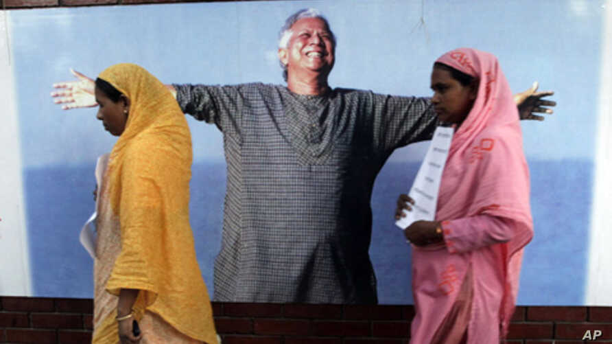 Employees of Grameen Bank walk in front of a portrait of Nobel laureate and bank founder Mohammad Yunus, Dhaka, Bangladesh, March 8, 2011.
