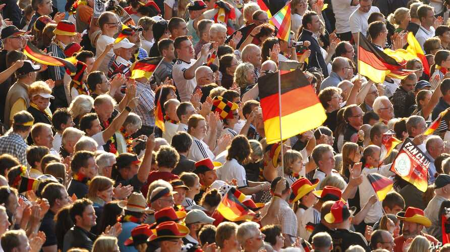FILE - The June 26, 2011 file photo shows soccer fans waving German flags during the group A match between Germany and Canada at the Women's Soccer World Cup in Berlin, Germany.
