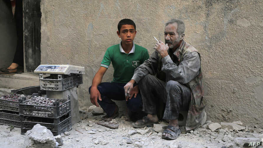 A man covered with dust sits on a street following a reported airstrike by Syrian government forces in the rebel-held neighborhood of Sukkari in the northern city of Aleppo, May 30, 2016.