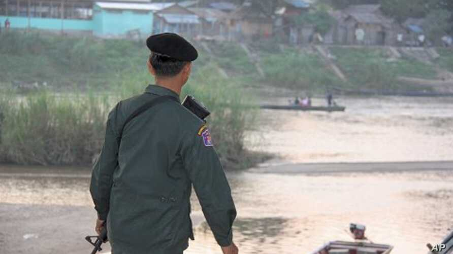 Thai soldier watches people who fled fighting take boats to and from Burma, Mae Sot, Thailand, 09 Nov 2010