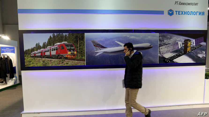 An Iranian man walks past the stand of the Russian company Poctex on December 22, 2015 during the Russia National Industrial Exhibition in Tehran.