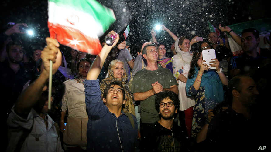 A group of jubilant Iranians cheer and spray artificial snow during street celebrations following the announcement of a landmark nuclear deal, in Tehran, July 14, 2015.