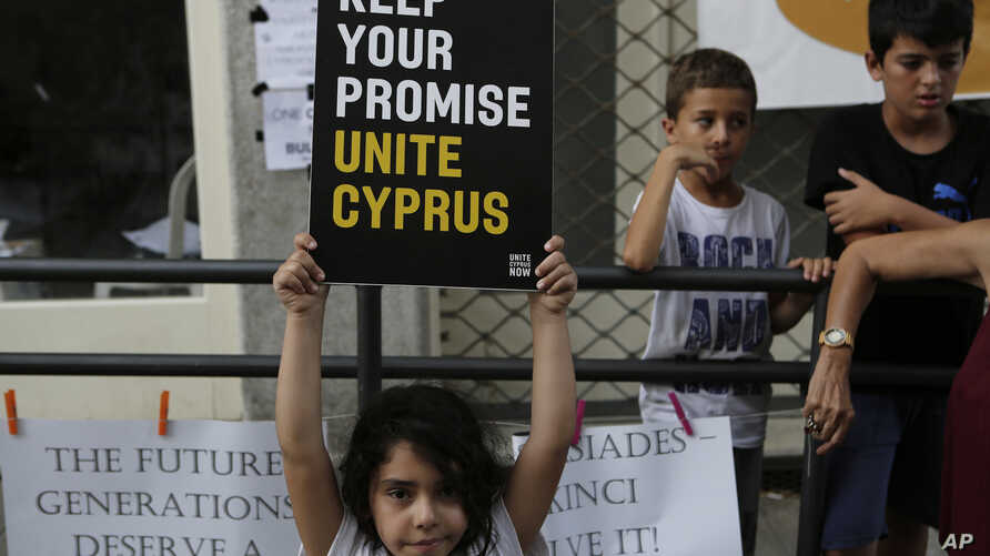 A girl holds a peace message during a peace protest at Ladras or Lokmachi crossing point that connects the Greek Cypriot south and the Turkish Cypriots breakaway north, inside the U.N buffer zone in central divided capital, Nicosia, Cyprus, July 6, 2...