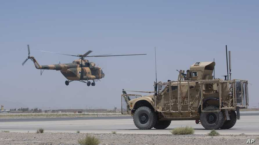 An Afghan National Army helicopter flies in as a U.S. military vehicle passes, at Kandahar Air Base, Afghanistan, Aug. 18, 2015.