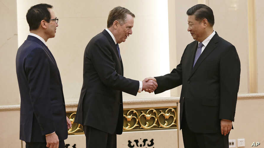 FILE - U.S. Trade Representative Robert Lighthizer, center, shakes hands with Chinese President Xi Jinping next to U.S. Treasury Secretary Steven Mnuchin, left, before their meeting at the Great Hall of the People in Beijing.