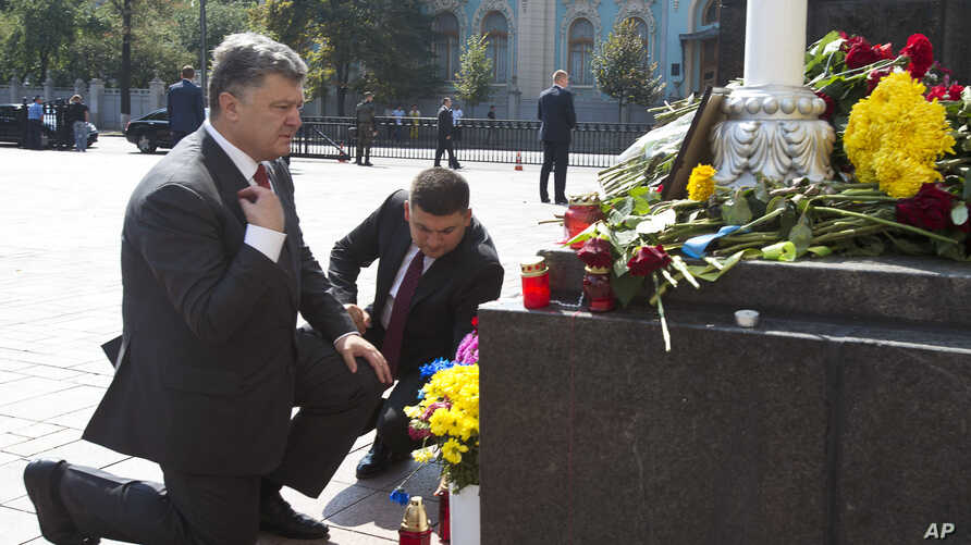Ukraine's President Petro Poroshenko (L) and parliament speaker Volodymyr Groisman lay flowers by the photo of a police officer who was killed in violent clashes Monday, in front of Parliament in Kyiv, Ukraine, Sept. 1, 2015.
