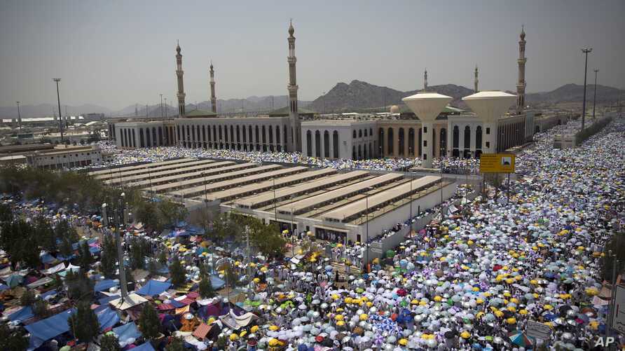 Muslim pilgrims hold umbrellas as they attend noon prayers outside the Namirah mosque on Arafat Mountain, during the annual Hajj pilgrimage, outside the holy city of Mecca, Saudi Arabia, Aug. 31, 2017.