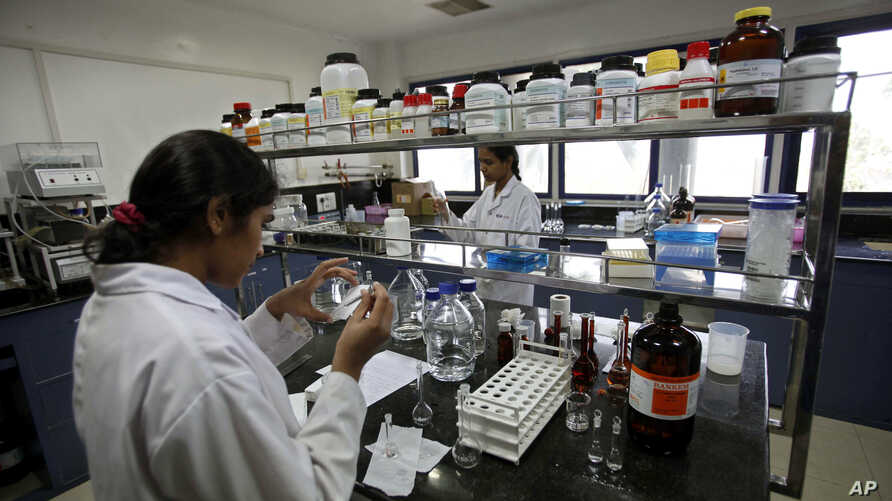 FILE - Indian scientists work inside a laboratory of the Research and Development Centre of Natco Pharma Ltd., in Hyderabad, India.
