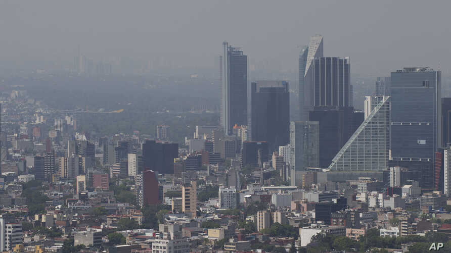 Haze hangs over Mexico City at midday, March 15, 2016. The Mexico City government declared its first air pollution alert in 11 years Monday after ozone levels reached almost twice the acceptable limit.