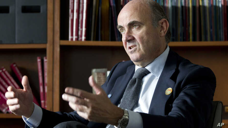 FILE - Spain's Economy Minister Luis de Guindos speak during an interview with The Associated Press at the IMF headquarters in Washington, April 17, 2015.