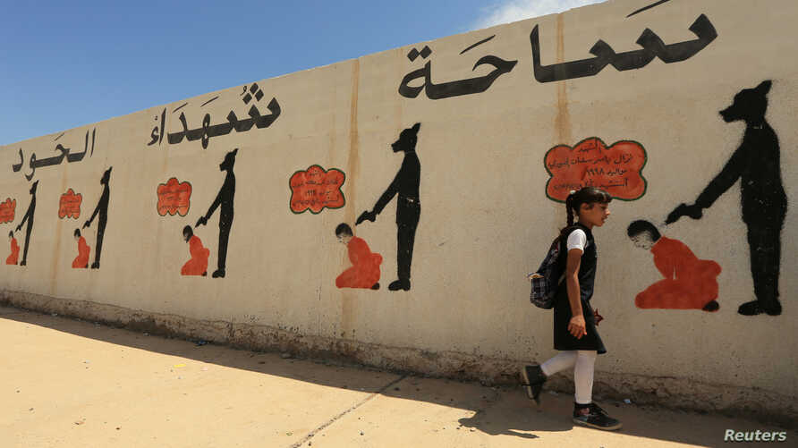 FILE - An Iraqi student walks past a school wall covered with drawings showing how Islamic State militants executed their prisoners in Mosul, Iraq, April 30, 2018.