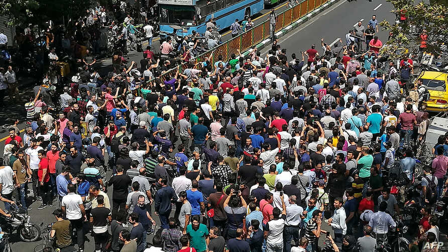 Iranian protesters shout slogans during a demonstration in central Tehran on June 25, 2018. Traders in the Iranian capital's Grand Bazaar held a rare protest strike against the collapse of the rial on the foreign exchange market.