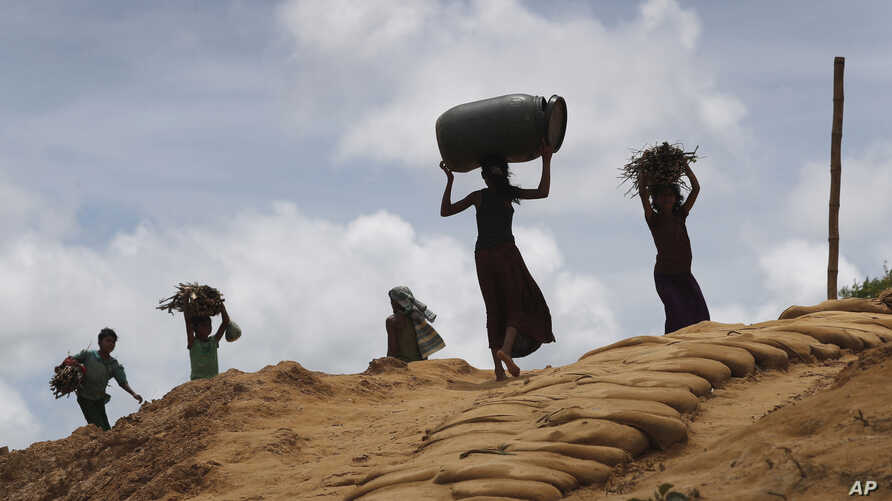 Rohingya girls carry firewood on their heads as they make their way through Kutupalong refugee camp, Thursday, June 28, 2018, in Bangladesh.