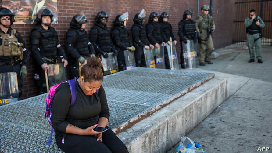 A woman checks her phone while police officers monitor the situation near a CVS pharmacy that was looted and burned by rioters on Monday after the funeral of Freddie Gray, on April 29, 2015 in Baltimore, Maryland.