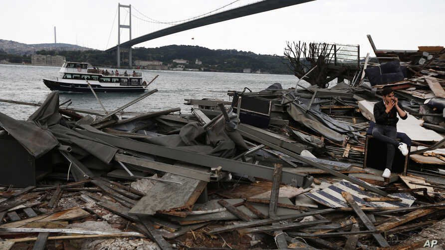 Backdropped by the Martyrs bridge over the Bosporus Strait, a man sits amongst the debris of the Reina nightclub that was attacked on New Year's Day, in Istanbul, Monday, May 22, 2017. Turkey's state-run news agency says authorities have partially de