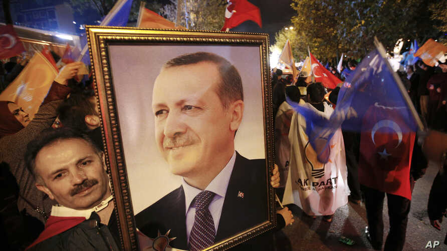 A supporter of the Justice and Development Party, (AKP), holds a portrait of Turkey's President Recep Tayyip Erdogan as people celebrate outside the AKP headquarters, in Istanbul, Turkey, late Sunday, Nov. 1, 2015.