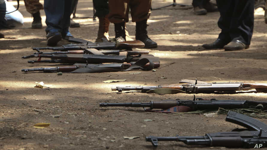 "FILE - Guns that belonged to child soldiers lie on the ground at a release ceremony, where they laid down their weapons and traded in their uniforms to return to ""normal life"", in Yambio, South Sudan, Feb. 7, 2018."