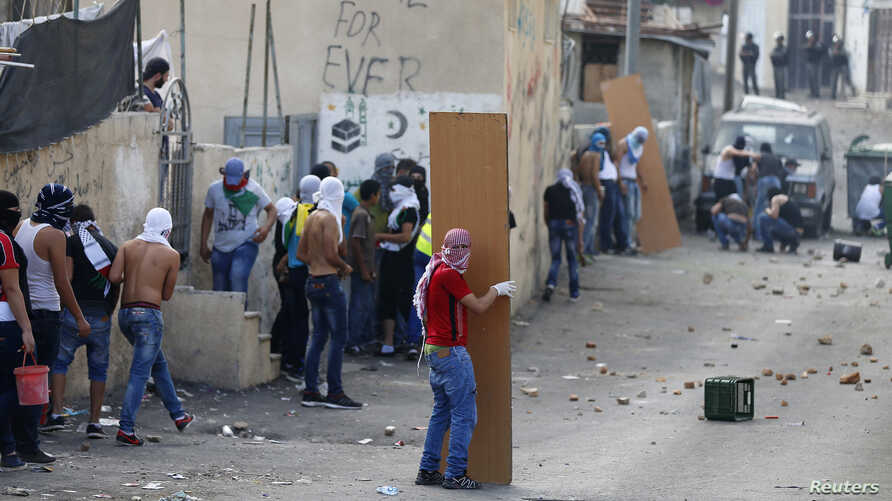A masked Palestinian hides behind a plank of wood during clashes in the East Jerusalem neighborhood of Wadi Joz, Sept. 7, 2014.