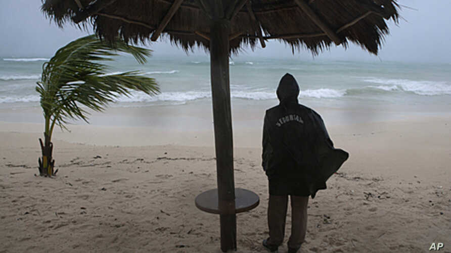 A security guard looks at the sea during a rain caused by Hurricane Rina in Playa del Carmen. The remnants of Hurricane Rina bore down on Cancun and other resorts on Mexico's popular Caribbean coast on Thursday, chasing away tourists and causing mass