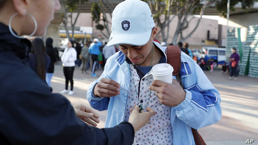 FILE - A man who only gave his first name as Ariel, of Honduras, receives an image of Saint Jude from a woman before crossing into the United States to begin his asylum case after being returned to Mexico, March 19, 2019, in Tijuana, Mexico.