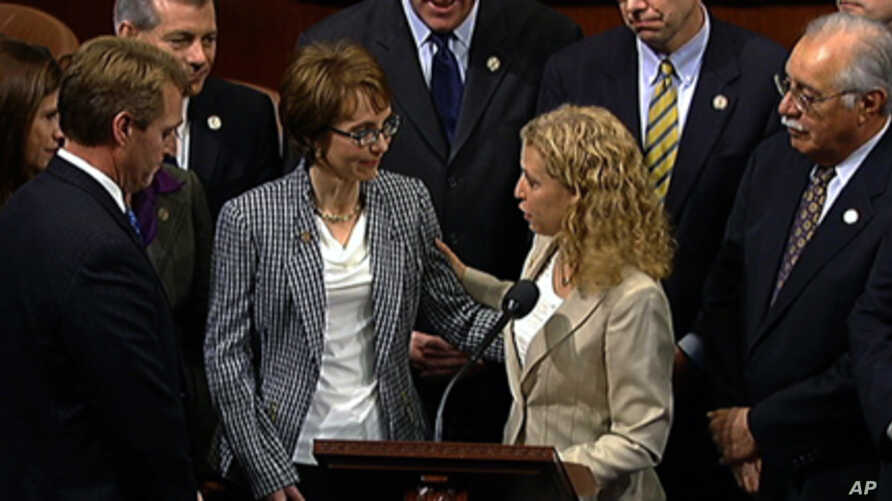This video image provided by House Television shows Rep. Gabrielle Giffords, D-Ariz., accompanied by Democratic National Committee Chair Rep. Debbie Wasserman Schultz, D-Fla., walks  on the floor of the House on Capitol Hill in Washington, Wednesday,