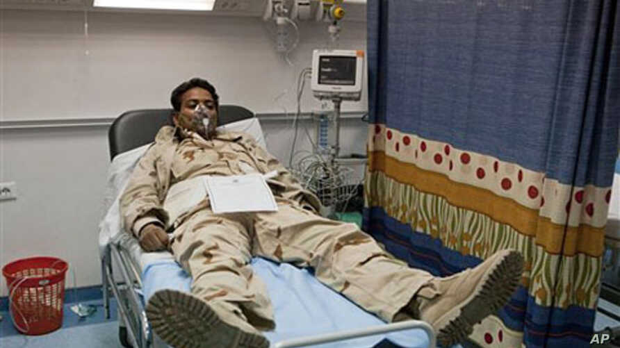 In this photo taken on a government organized tour, a Libyan soldier wearing oxygen mask lies at Khadra Hospital in Tripoli, Libya following an air strike, May 12, 2011