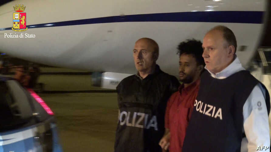 This handout picture released by the Italian police (Polizia di Stato), on June 8, 2016  shows Medhanie Yehdego Mered, 35, an Eritrean suspected of controlling a migrant trafficking network, escorted by policemen upon his extradition from Sudan to It