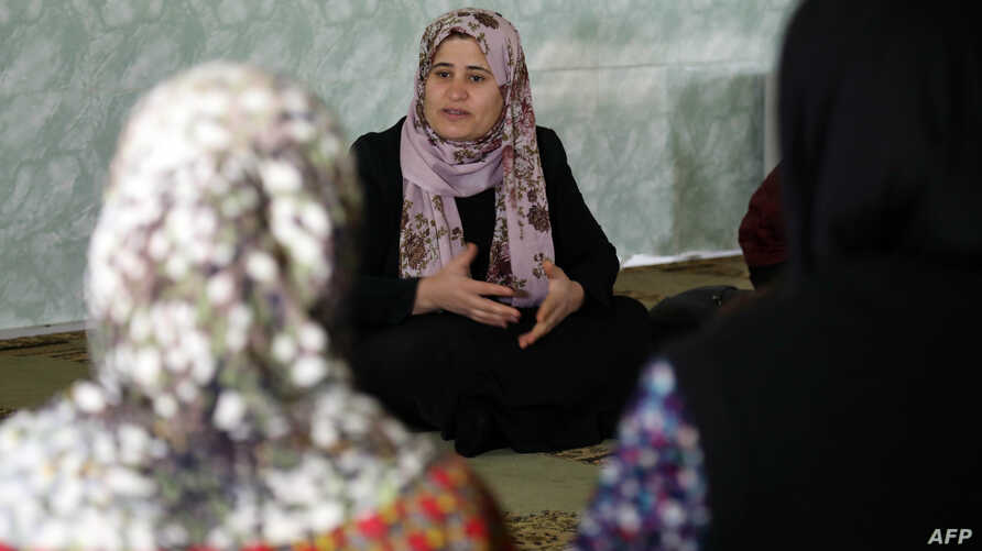 Rasul, center, an Iraqi Kurdish activist with the nonprofit organization WADI, speaks to women and young girls about the harms of genital mutilation in Sharboty Saghira, a small village east of Irbil, Dec. 3, 2018.