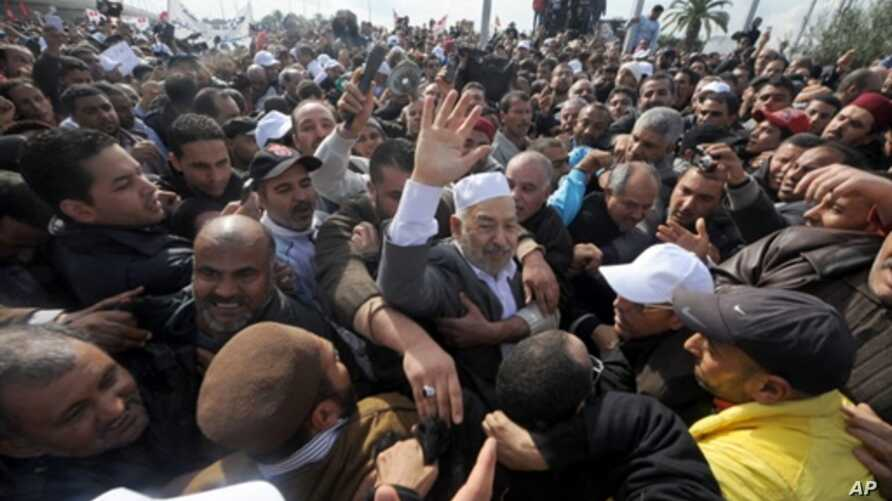 Rached Ghannouchi, the leader of Tunisia's Islamist movement Ennahdha, waves upon arrival in Tunis after 22 years in exile on January 30, 2011