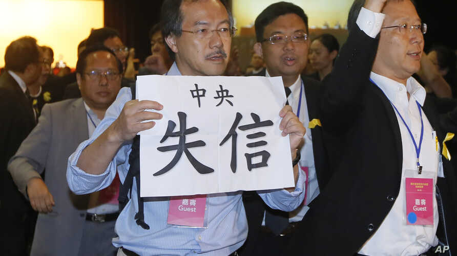 """FILE - Pro-democracy lawmaker Fernando Cheung holds a placard which reads """" Central Government break the promise """" as he protests against Li Fei, deputy secretary general of the National People's Congress Standing Committee, during a briefing sessi..."""