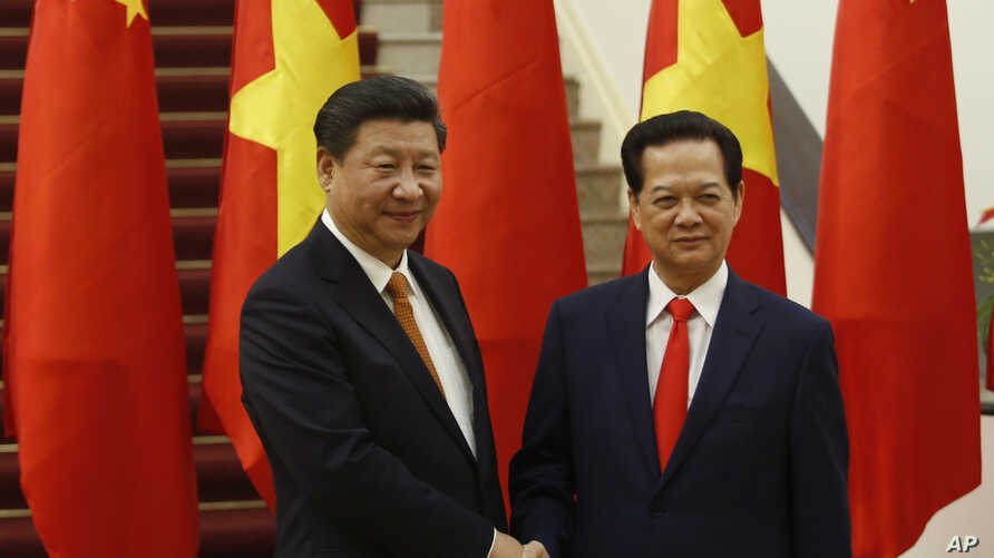Chinese President Xi Jinping, left, poses for a photo with Vietnam's Prime Minister Nguyen Tan Dung before their meeting at the Government Office in Hanoi, Nov. 5, 2015.