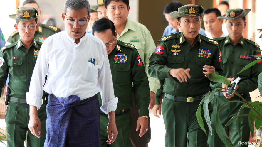 FILE -  Rakhine Chief Minister Nyi Pu, left, and Myanmar's high ranking military officers walk after a daytrip with a diplomatic mission and United Nations officials to the Maungdaw area in northern Rakhine State in Myanmar,  Nov. 3, 2016.