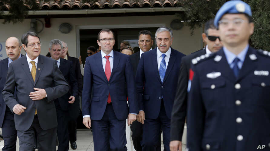 FILE - In this Wednesday, Nov. 25, 2015, file photo, Cyprus President Nicos Anastasiades, left, Turkish Cypriot leader Mustafa Akinci, right, and U.N. envoy Espen Barth Eide, center, leave after their meeting at the U.N.-controlled abandoned Nicosia