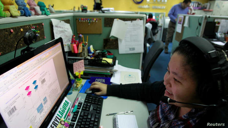FILE - A call center agent talks to a client in the U.S. as she works the overnight shift in Manila's Makati financial district, Feb. 6, 2012.