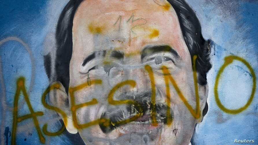 """The Spanish word for """"murderer"""" covers a mural of Nicaragua's President Daniel Ortega, May 26, 2018, as part of anti-government protests demanding his resignation in Managua, Nicaragua."""