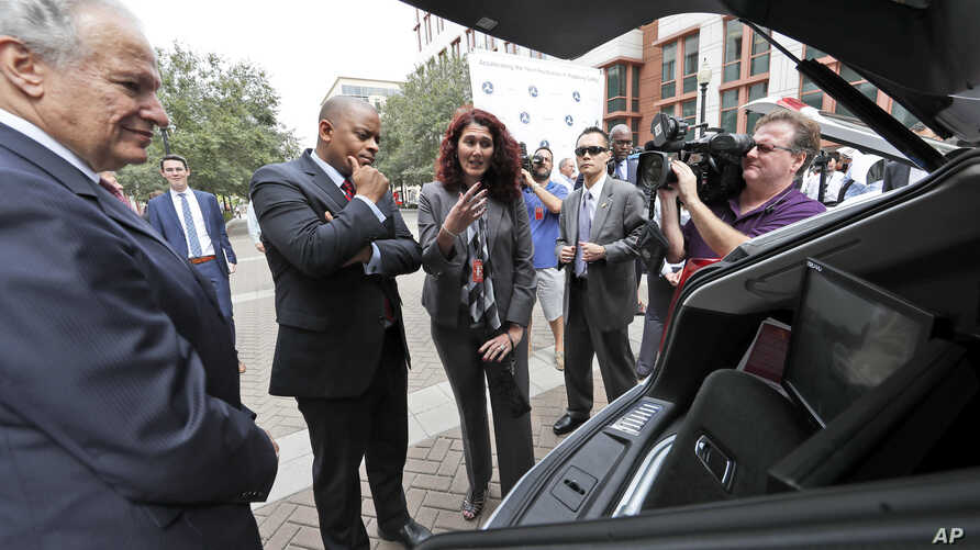 Self Driving Cars: National Highway Traffic Safety Administration Administrator Mark Rosekind, left, and Transportation Secretary Anthony Foxx, listen to Myra Blanco, with Virginia Tech's transportation Institute, talk about their car after a news co