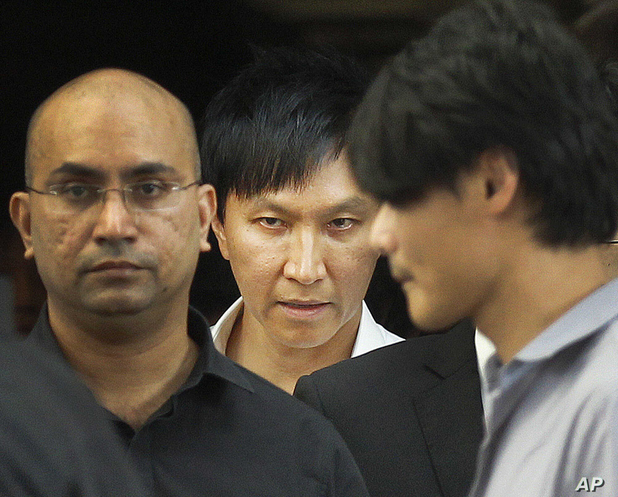 FILE - City Harvest Church founder Kong Hee, center, is surrounded by supporters as he leaves the Subordinate Courts Wednesday, June 27, 2012 in Singapore.