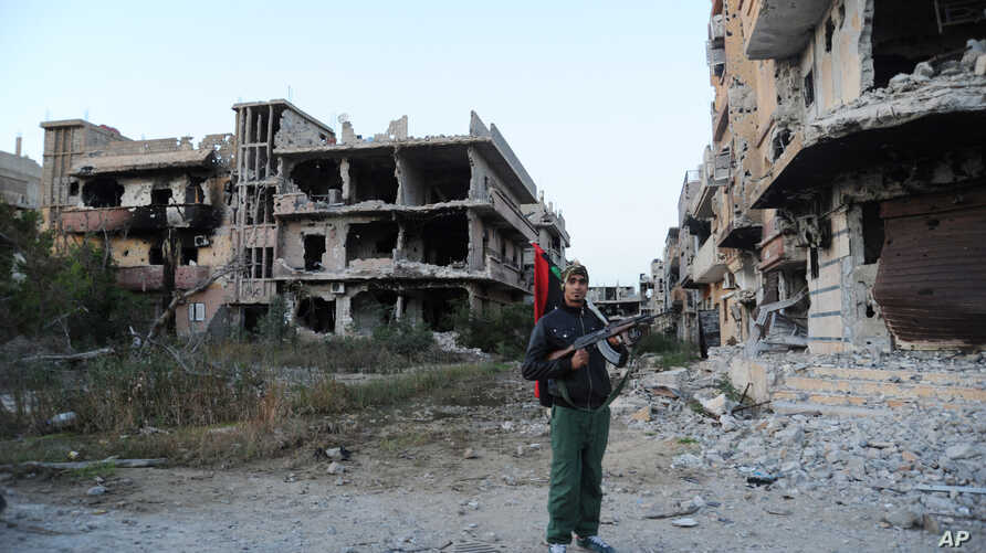 FILE - A civilian fighter holding the Libyan flag stands in front of damaged buildings in Benghazi, Libya, Feb. 23, 2016.