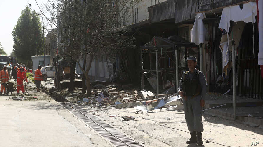 Municipality workers clean up at the site of a suicide attack in Kabul, Afghanistan, July 24, 2017.