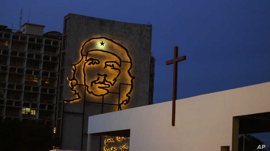 """A sculpture of revolutionary hero Ernesto """"Che"""" Guevara is lit up on a government building in Revolution Square beside an altar under construction ahead of Pope Francis' Mass in Havana, Cuba, Sept. 10, 2015."""