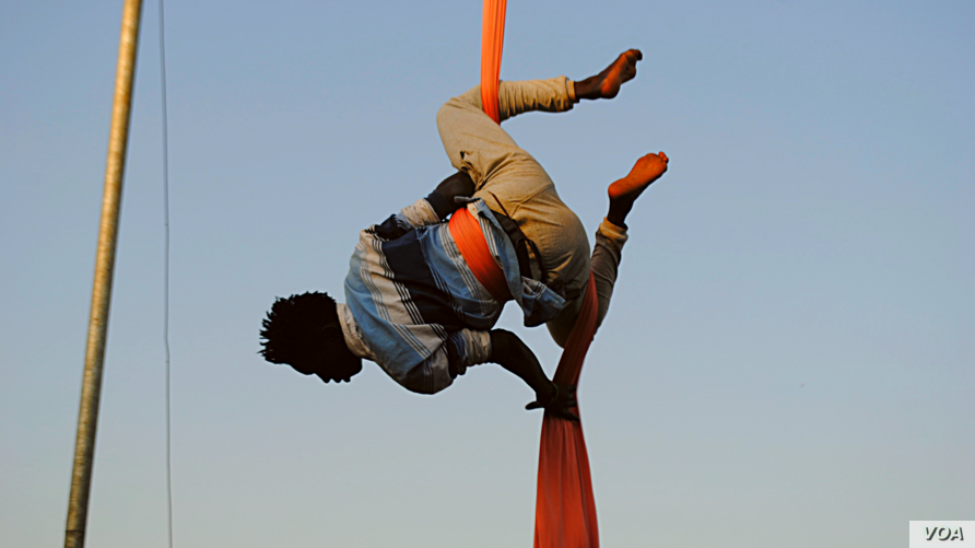 One of the Uganda's Hiccup Circus's aerialists gets into position to perform what's known as a 'drop'. This will send him on a breathtaking spin towards the ground, and is a common move during a routine's finale. (Elizabeth Paulat/VOA)